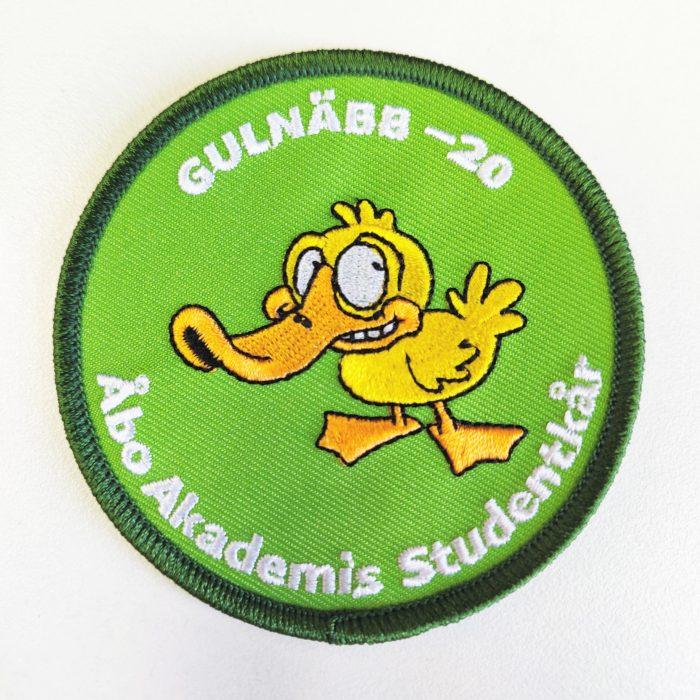 Gulnäbbsmärke 2020, mörkgrön kant, limegrön bakgrund, en gul anka i mitten och text gulnäbb 2020 Åbo Akademis Studentkår